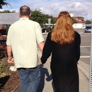 Image of Maureen walking and holding hands with husband.