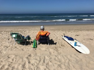 A man sitting at the beach with a beach chair and surfboard.