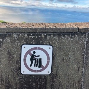 Image of a sign asking people not to climb over a wall at the Cliffs of Moher