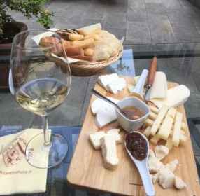 Image of cheeseboard and wine at Cantina Follie