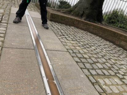 Image of feet straddling the Prime Meridian